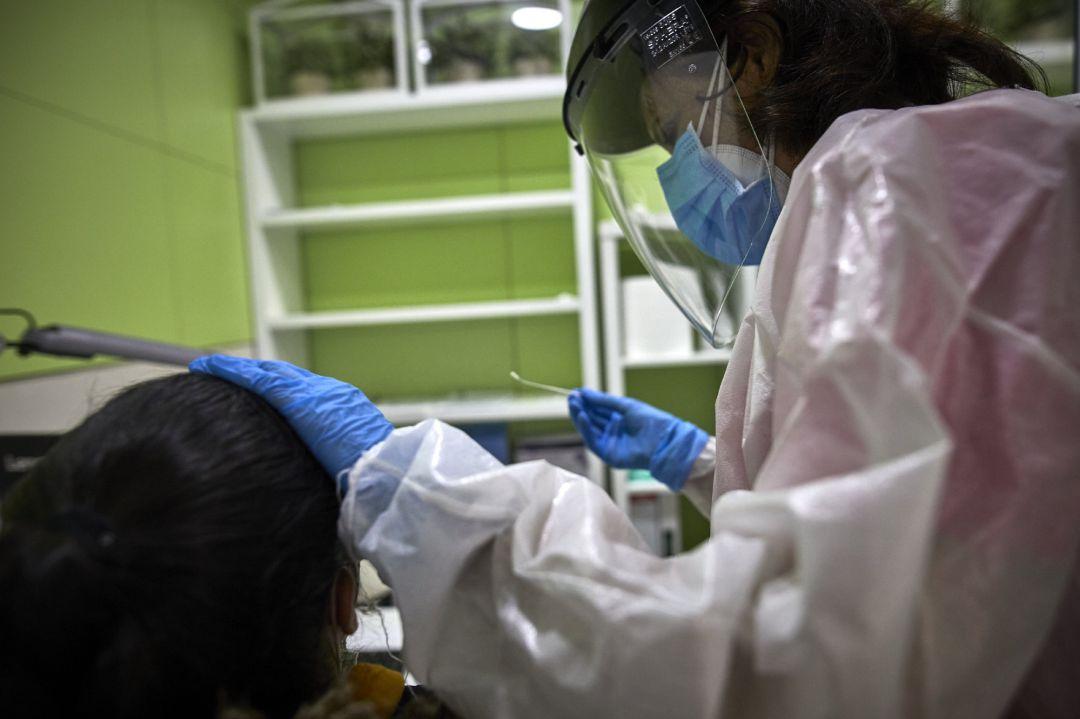 Una profesional sanitaria atiende a una paciente