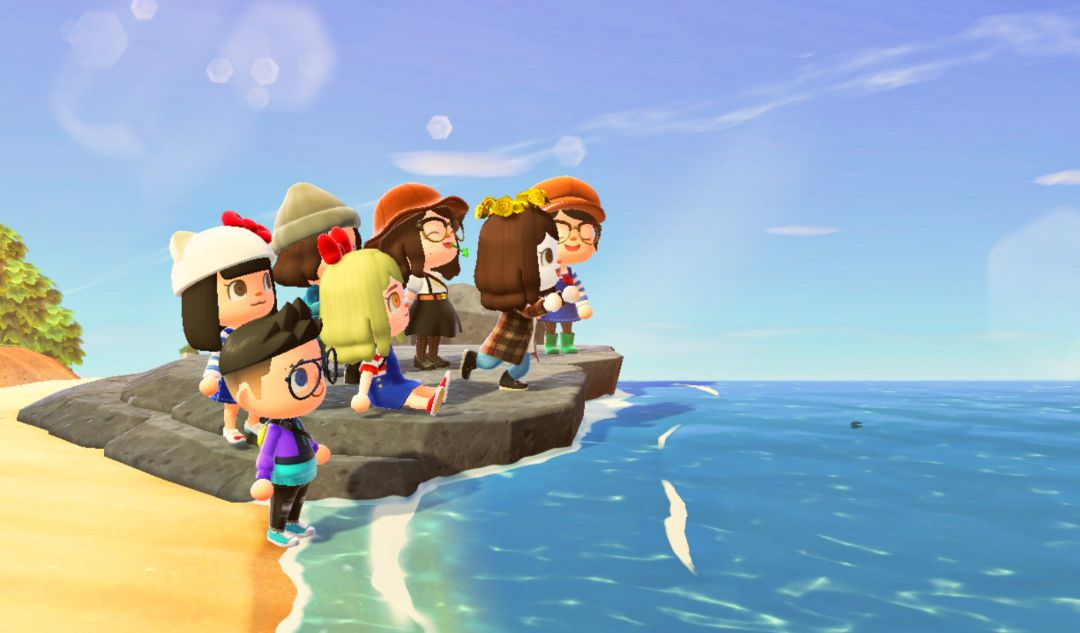 Grupo de amigos en la playa de una isla de Animal Crossing: New Horizons.