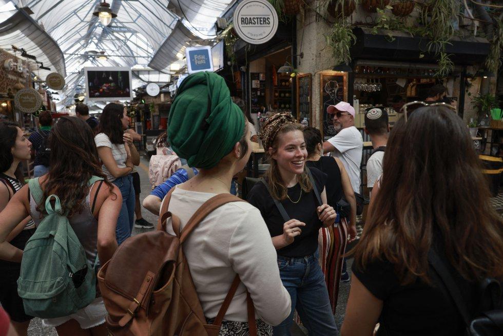 Un grupo de chicas conversan sin mascarilla en un mercado de Jerusalem.