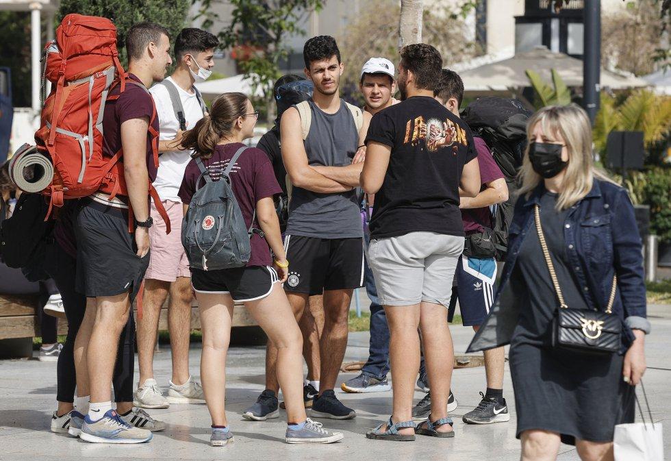 Un grupo de amigo conversan sin mascarilla en la costa de Tel Aviv.