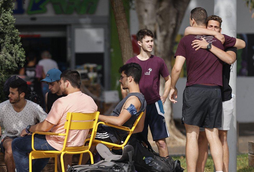Dos amigos se abrazan en el primer día sin uso obligatorio de mascarillas al aire libre en Israel.