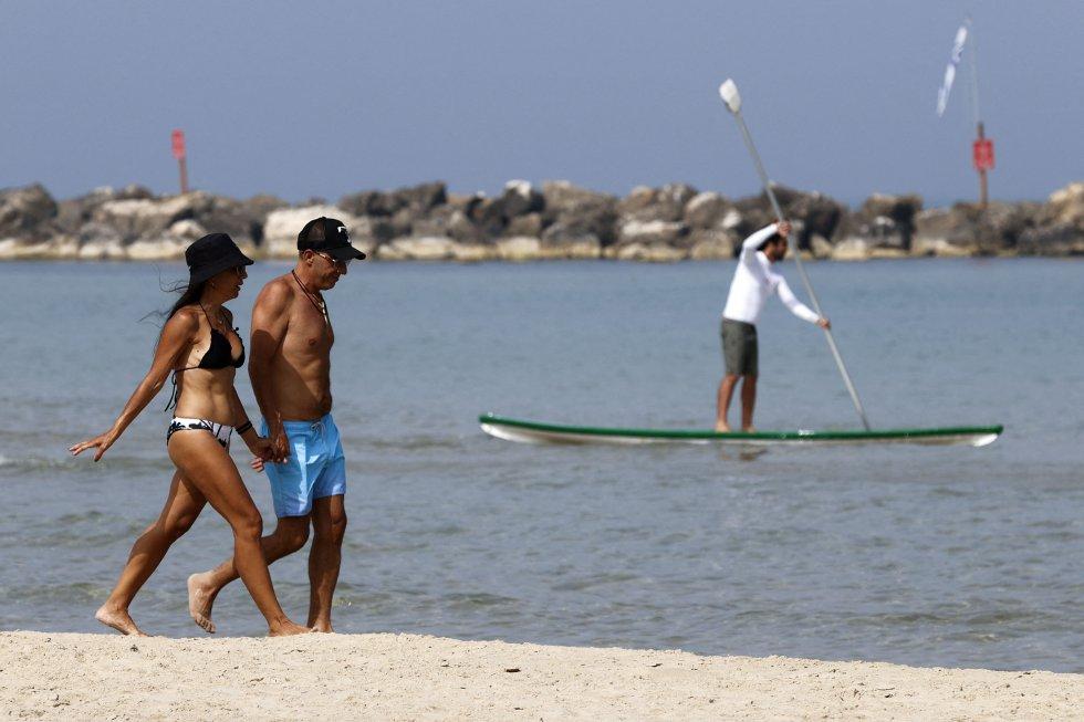 Una pareja pasea sin mascarilla por la playa de la ciudad costera israelí de Tel Aviv.