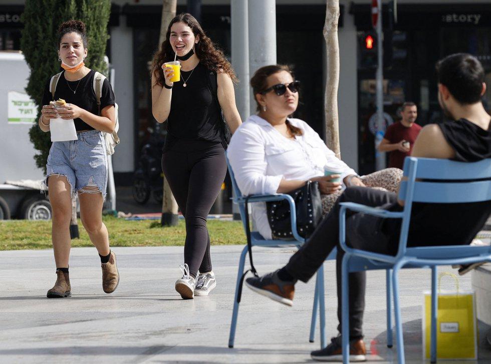 Dos chicas conversan sin mascarilla en una terraza de Tel Aviv.