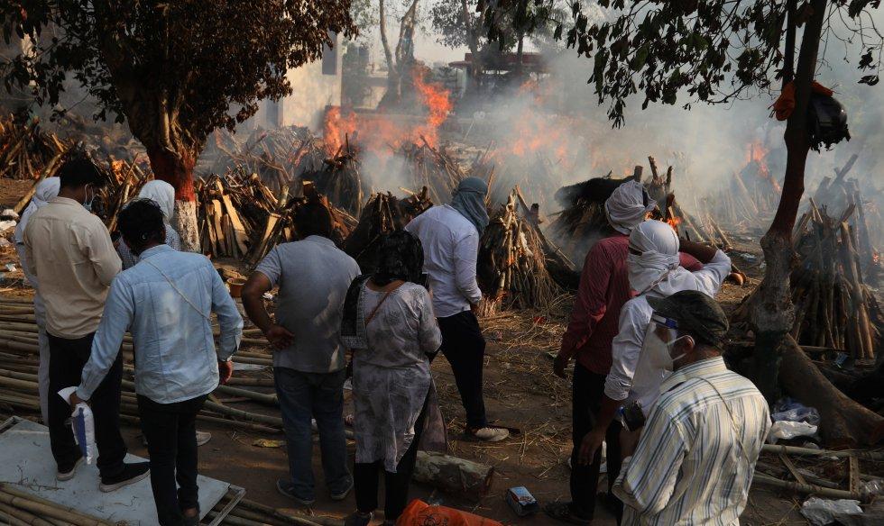 Miembros de familias observan las piras para incinerar los cuerpos de personas muertas por COVID.
