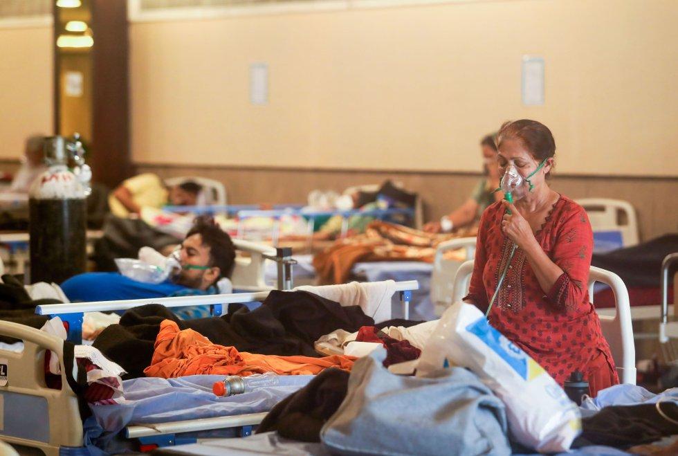 Un paciente lleva con una mascarilla de oxígeno en una sala de baile convertida en hospital.