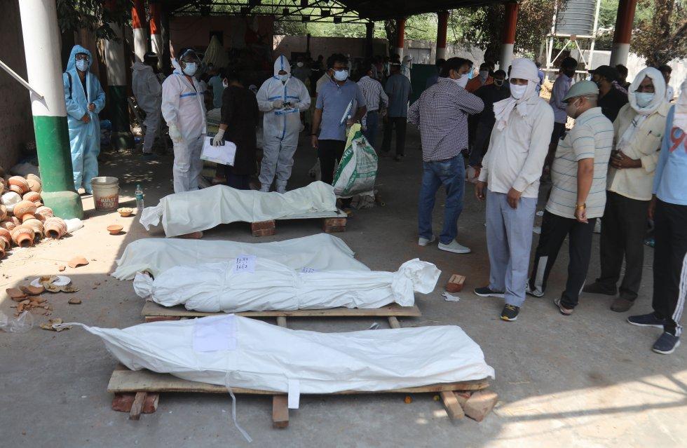 Un grupo de personas, la lado de los cuerpos de las personas fallecidas por COVID, esperan el momento de la cremación en Ghazipur.