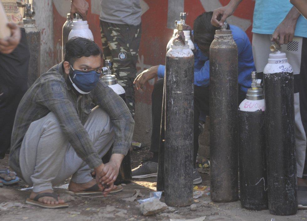 Un grupo de personas esperan con cilindros de oxígeno vacíos a la espera de ser rellenados con oxígenos en Talkatora.