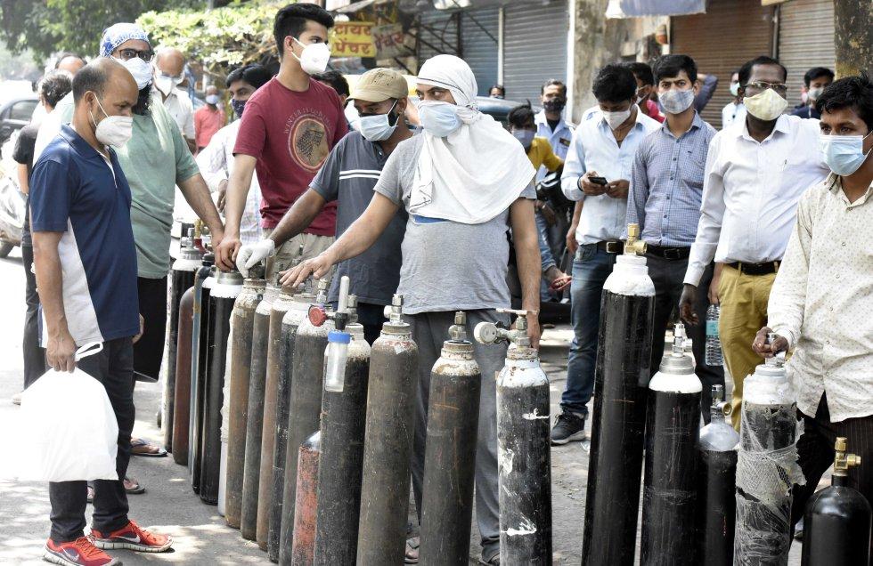 Un grupo de personas esperan a rellenar los cilindros de oxígeno.