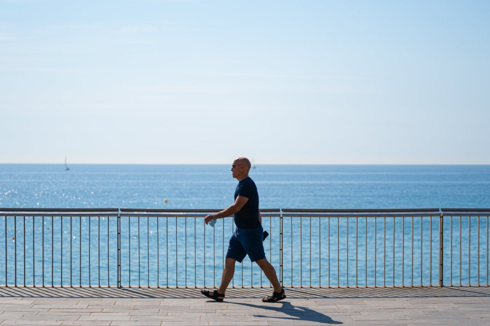 Un hombre pasea sin mascarilla por la Barceloneta, en Barcelona