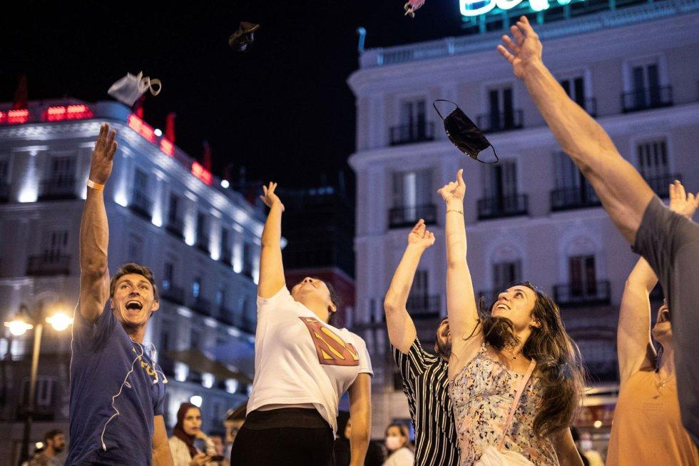 Varias personas celebran el fin del uso obligatorio de la mascarilla en espacios abiertos en la Puerta del Sol, en Madrid