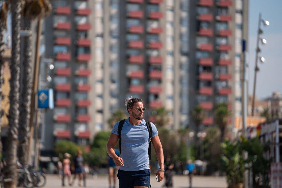Un chico pasea sin mascarilla por la Barceloneta, en Barcelona