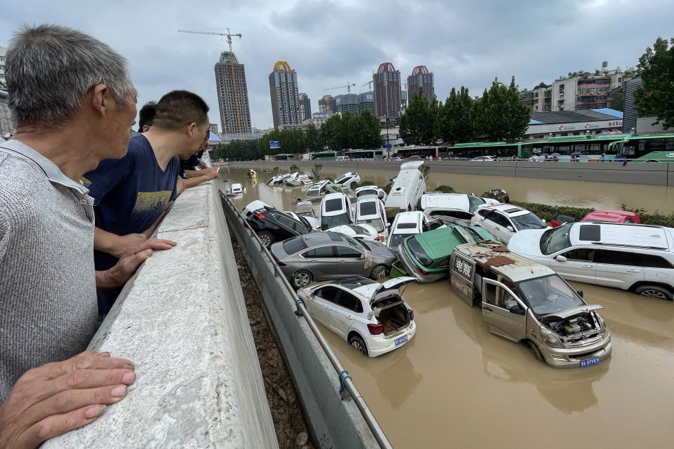 Un grupo de personas mira los coches acumulados en una riera en Zhengzhou.