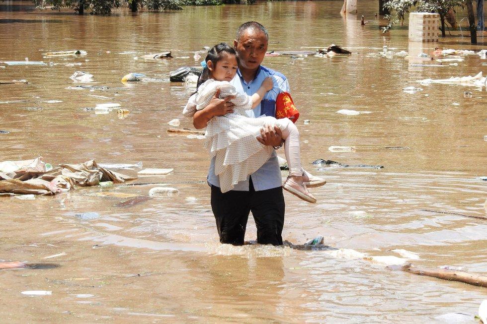 Un hombre evacúa a una niña en Dazhou (provincia de Sichuan).